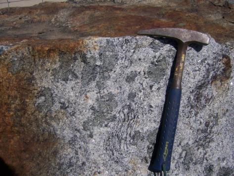 Según quien la vea, esto puede ser un granito de anatexia o una migmatita tipo diatexita. Los grandes nódulos verdosos son cordierita. Aunque la mayor parte de la roca está fundida quedan algunas partes sin fundir que se reconocen por la presencia de una fábrica planar.